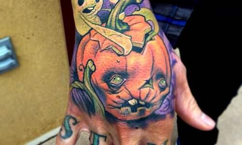 Tatuaje de calabaza en la mano, la palabra STAY en los nudillos