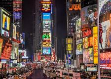New York Times square at night, brightly lit and busy.