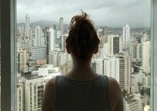 Woman looking at city outside window