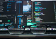Glasses frame on a desk in front of a busy computer screen displaying code