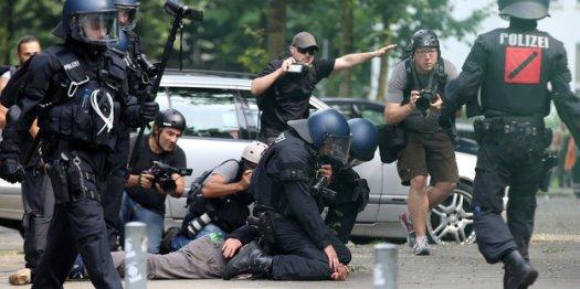 Polizisten drücken einen Mann auf den Boden, ein Mann im Hintergrund hält einen Fotoapparat