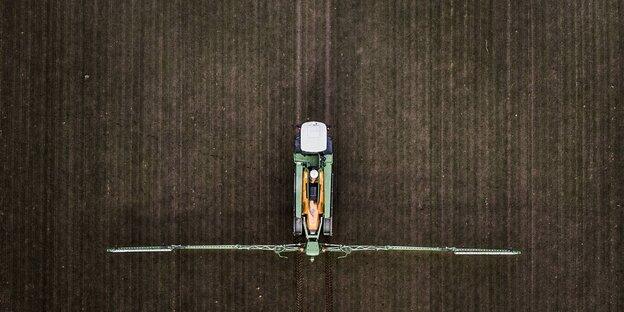 Ansicht von oben auf einen Traktor, der auf einem Feld Pestizide versprüht