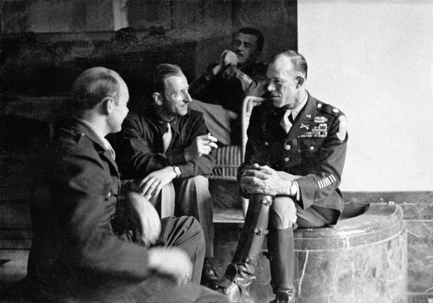 Alice's son Otto, sitting in civilian clothes, talking to a US major