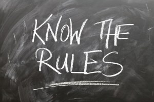 """chalkboard writing of """"know the rules"""" to illustrate business compliance regulations"""