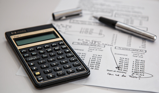 """Photo of black calculator on top of sheet of paper with budget calculations and the note """"Can we do this?"""" hand written on it."""