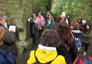 Rachel Moss points out features on the cross head at St. Mullins.