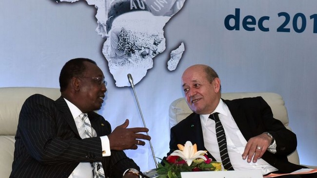 """French Defence Minister Jean-Yves Le Drian (R) speaks to Chadian President Idriss Deby Itno as they attend the last day of the International Forum on Peace and Security in Africa in Dakar on December 16, 2014. Malian President Ibrahim Boubacar Keita called on the world community to put an end to instability in southern Libya, which he called a """"hornet's nest"""" and a """"fabulous market of weapons to our countries."""" AFP PHOTO / SEYLLOU"""
