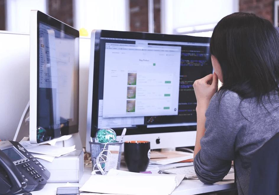 woman behind computer monitor