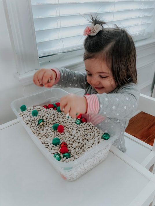 Make a Christmas sensory bin for your toddlers as a festive activity this holiday season. This will improve their senses and fine motor skills