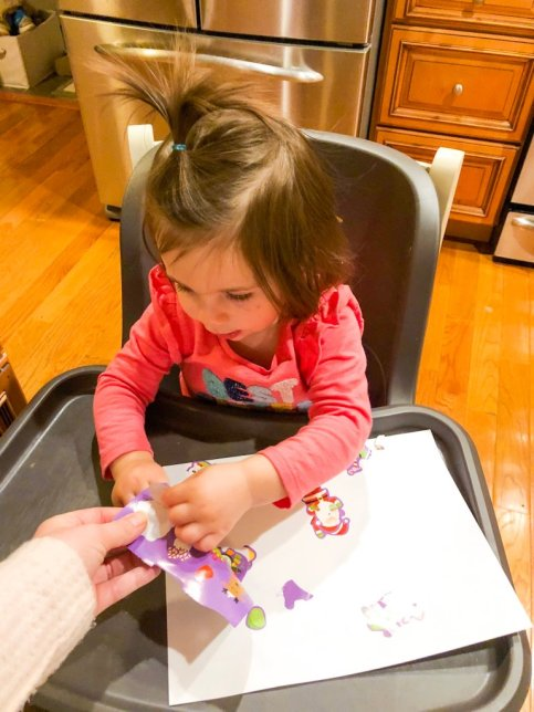 Christmas activity using stickers for your toddler that incorporates language, fine motor skills, and hand eye coordination.