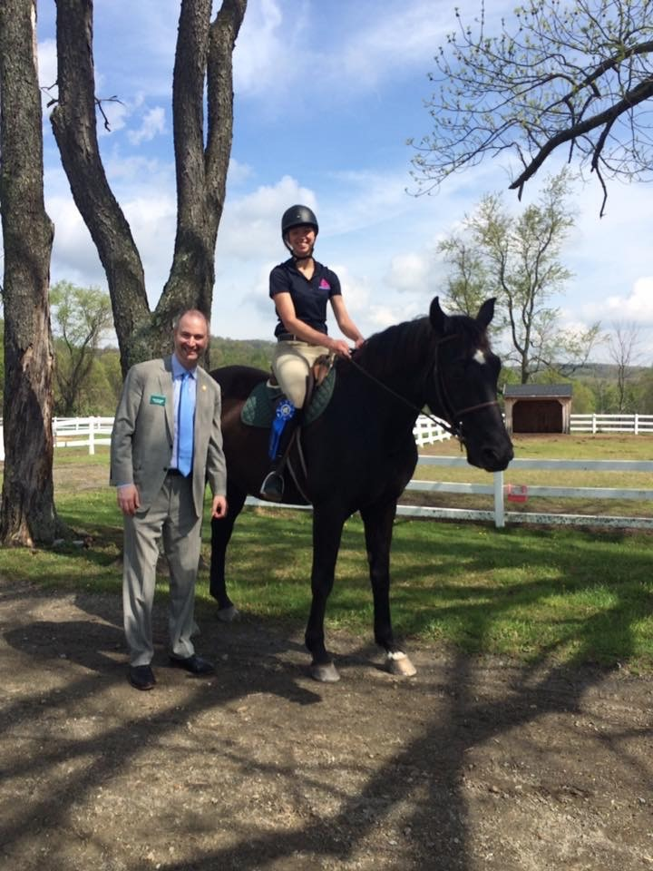 Kevin Pendergast, Head of the Kildonan School, stands next to a student who is on a horse.