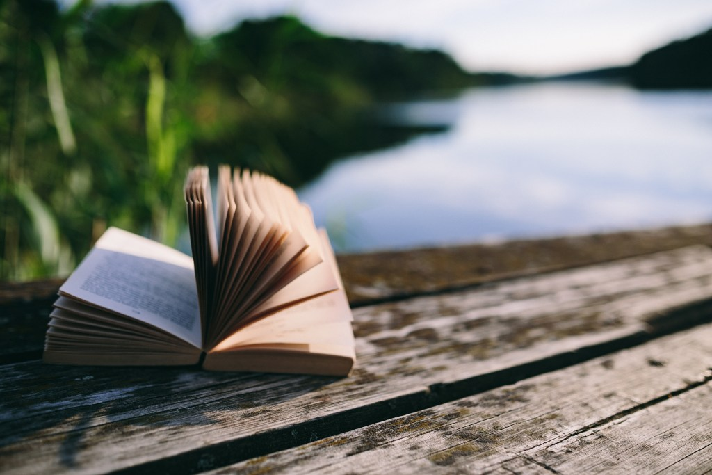 An open book on a dock by a lake