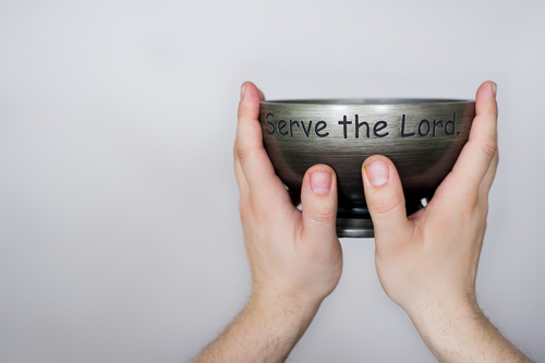 Uplifted hands holding a bowl which says, serve the Lord