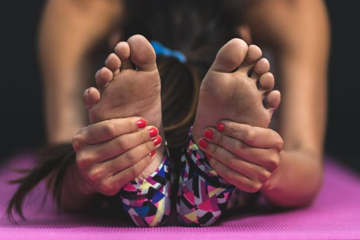 stretching-woman-hands-feet-de-stress-with-yoga