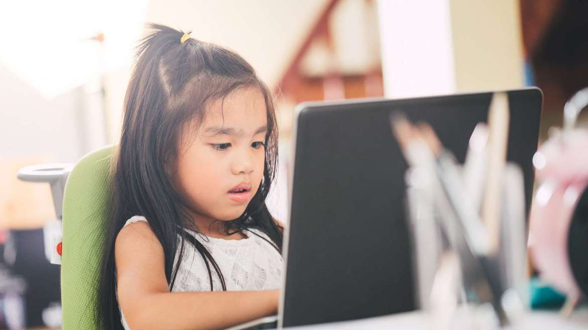 A young girl works on a school assignment on a laptop.