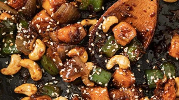 Spicy Cashew Chicken in a skillet with a wooden spoon