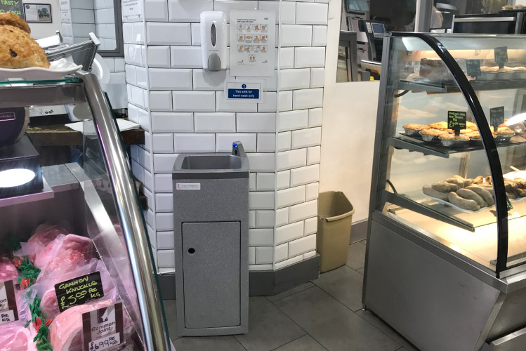 The Teal portable hand wash unit is situated between deli and fresh meat counters