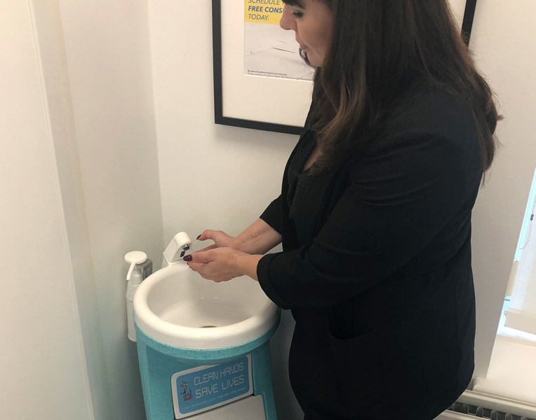 The Medical Director washes hands using Hygienius hand wash unit