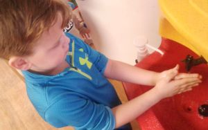 A boy being taught how to wash his hands with a KiddiSynk