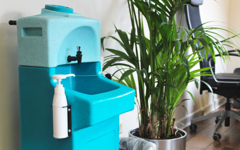 A washstand portable hand wash unit placed at the entrance to an office