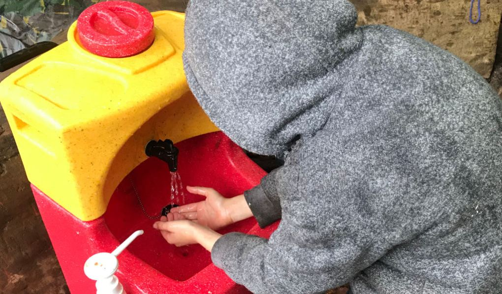 A child washing hands at a forest school with a KiddiSynk