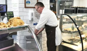 Farm shop worker washing hands with a portable sinks after touching raw meat