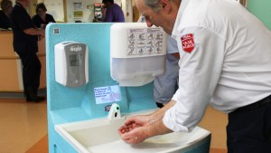 Person washing hands with a MediWash portable unit that features handwashing instruction video