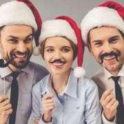 Karriere auf Weihnachtsfeier fördern drei Mitarbeiter vor Fotobox und mit Weihnachtsmützen
