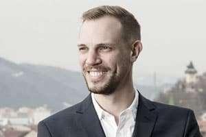 Thomas Kriebernegg aus Graz vor Uhrturm. Mann schaut nach links. Portrait