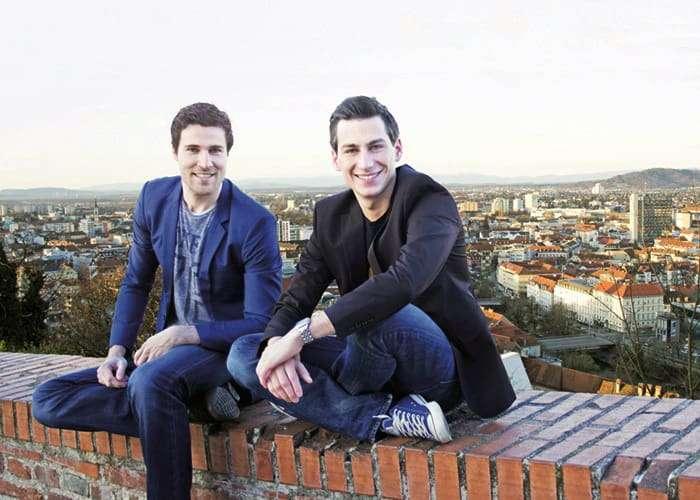 Gründer Andreas Mairold und Paul Stanzenberger sitzen auf Steinmauer am Schlossberg