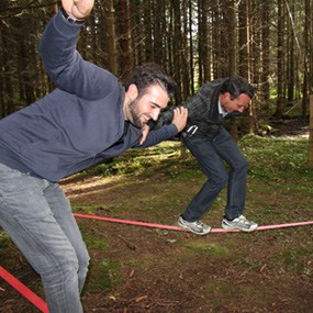 Zwei Teammitglieder versucht als Teambuilding Aufgabe über eine Slackline zu gelangen