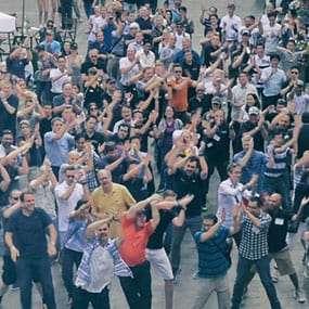 Großes Team feiert seinen Erfolg mit einem öffentlichen Flashmob
