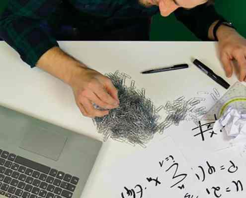 Mann mit Büroklammern am Schreibtisch und Laptop daneben