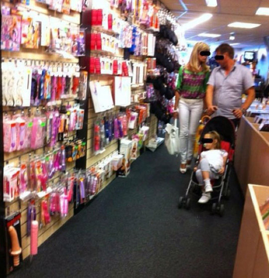 mom and dad in adult book store sex store with baby in stroller Worst Parents Bad Parents Bad Parenting Moms Dads Awkward Family Photos Stupid Parents Crazy Bad Example Terrible Horrible Awful Weird buying sex toys