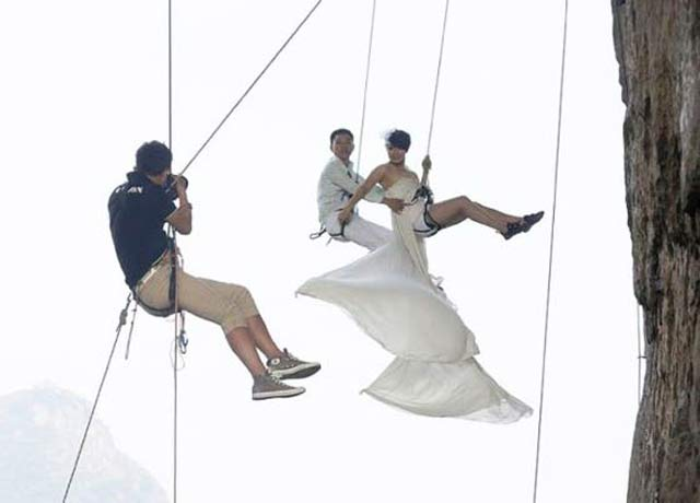 Bride & Groom handing from cliff ~ 14 Funny Wedding Photos