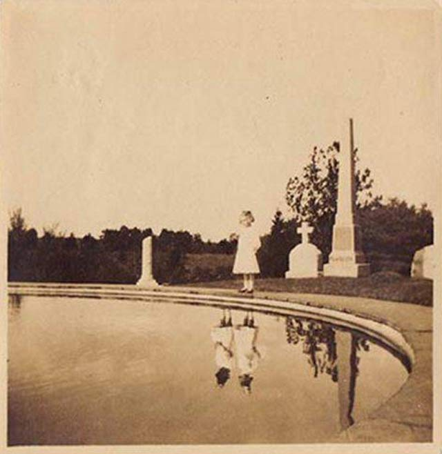 Girl has 2 reflections in cemetery pool ~ 25 Creepy Photos