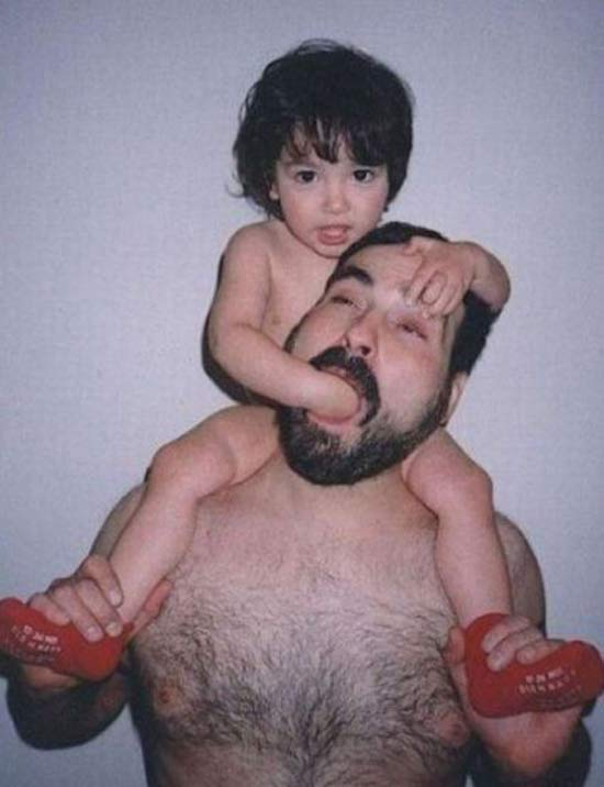boy on dad's shoulders with hand shoved in dad's mouth ~ 18 Funny Awkward Family Photos