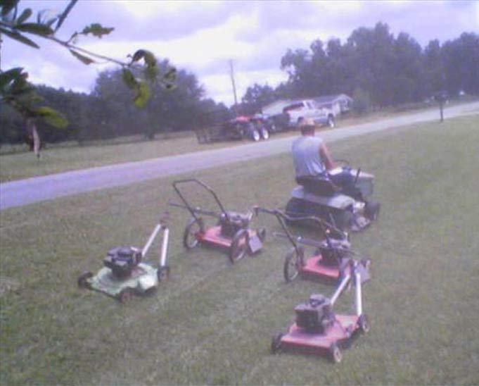 Redneck lawn mowing: Pulling four push mowers behind tractor
