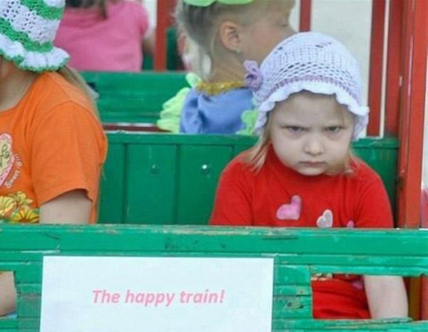 Awkward photo of mad, frowning girl on happy train