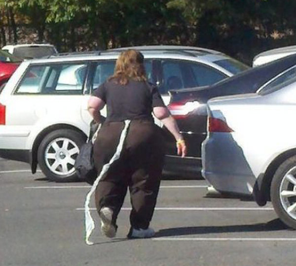 Awkward snapshot of woman in Walmart parking lot with toilet paper hanging from her pants