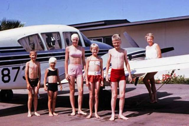 vintage color snapshot kids in swimsuits and bathing caps standing next to plane