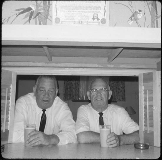 Vintage snapshot 1950s two old guys with drinks peering though shutters in basement tiki bar