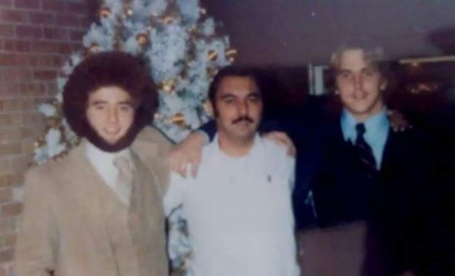 Classic 1970sphoto of three men one with great afro and beard posing in front of a white christmas tree