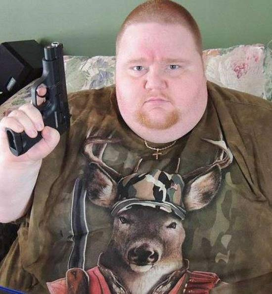 Fat man ginger in shirt with deer and came holding up a pistol