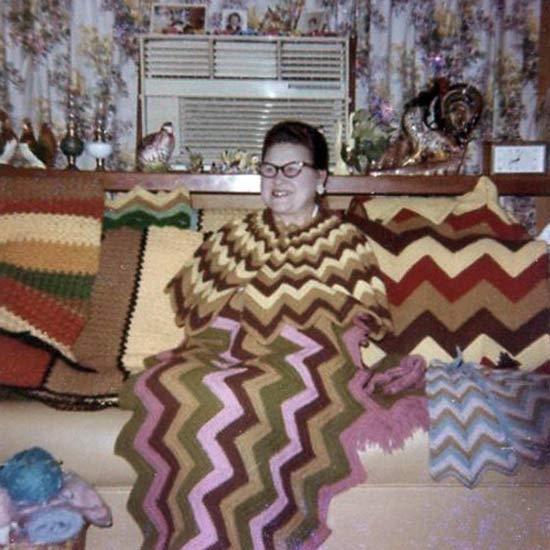 Vintage color snap shot of woman in couch in knitted dress that matches the knitted wavy lined afghan on couch