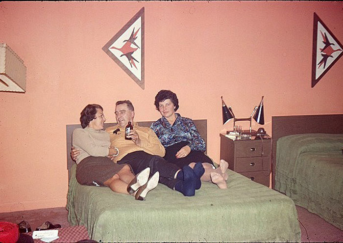 Awkward vintage snap from 1950s motel room, man drinking beer on bed with two women