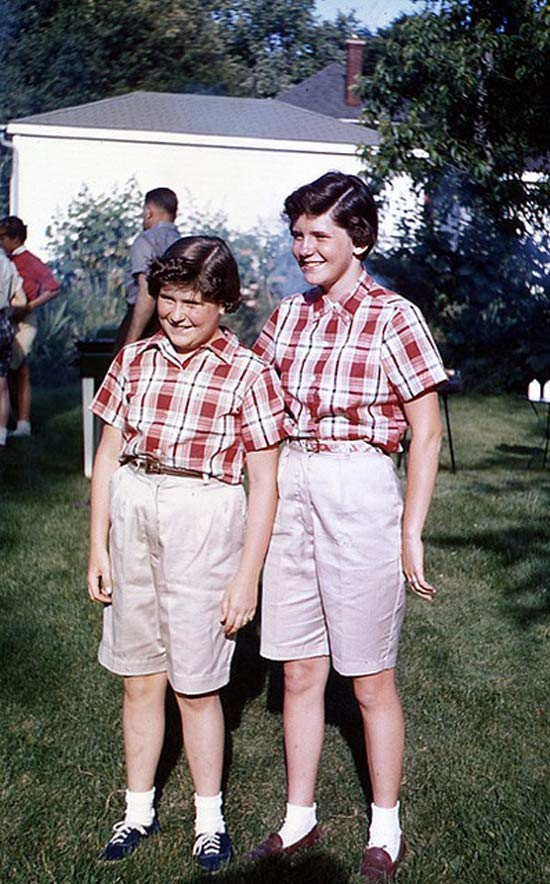 Awkward vintage color snap of sisters dressed identical, 1960s