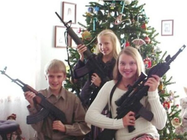 Funny Awkward Christmas Photos ~ kids posing in front of tree with weapons, AK 47s