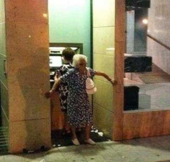old woman, grandma blocking atm machine, guarding another woman, protecting the pin number