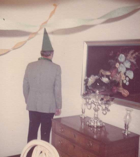 vintage color snapshot of man at party standing in corner with dunce cap